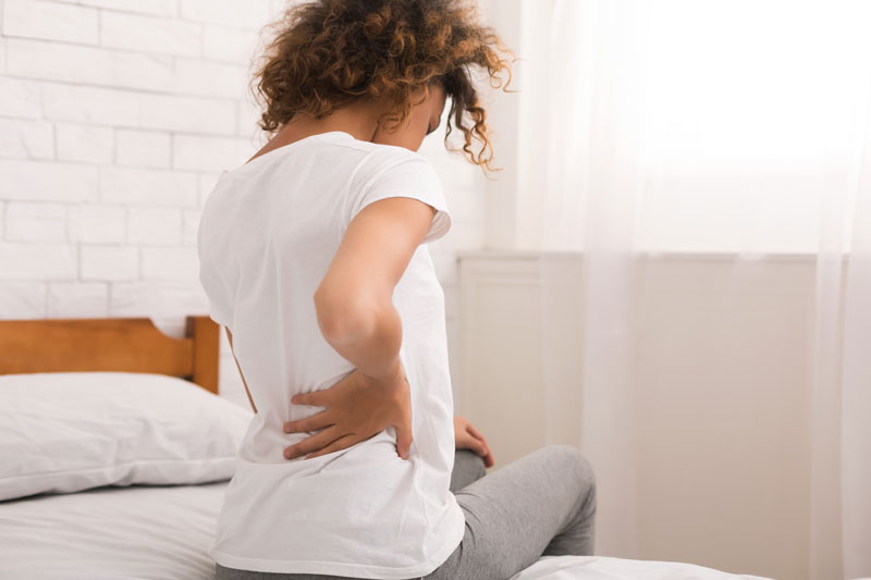 woman in bed with sciatica back pain